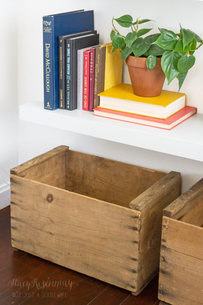 crates under a bookshelf for additional storage