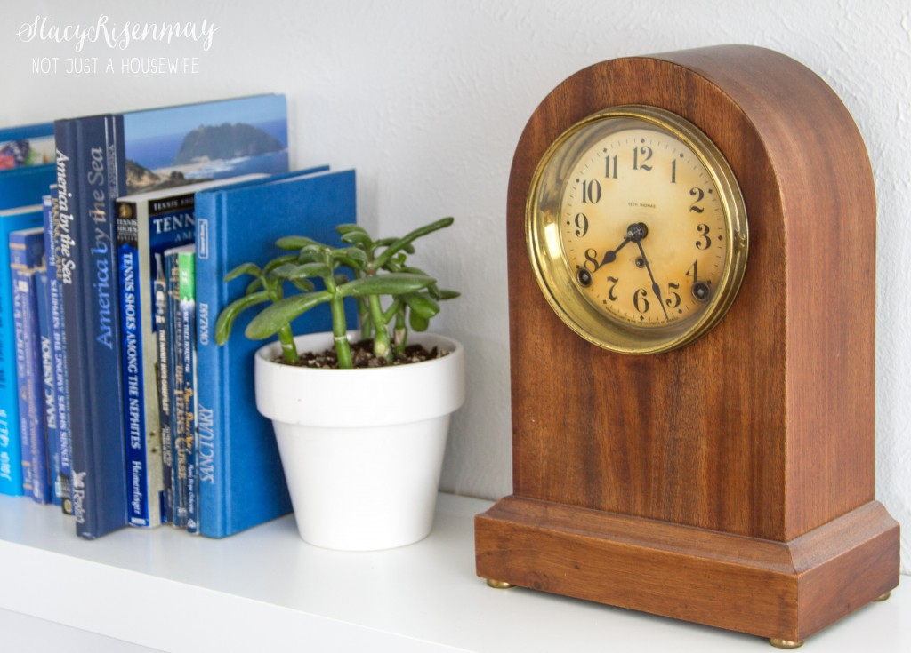 antique clock on bookcase
