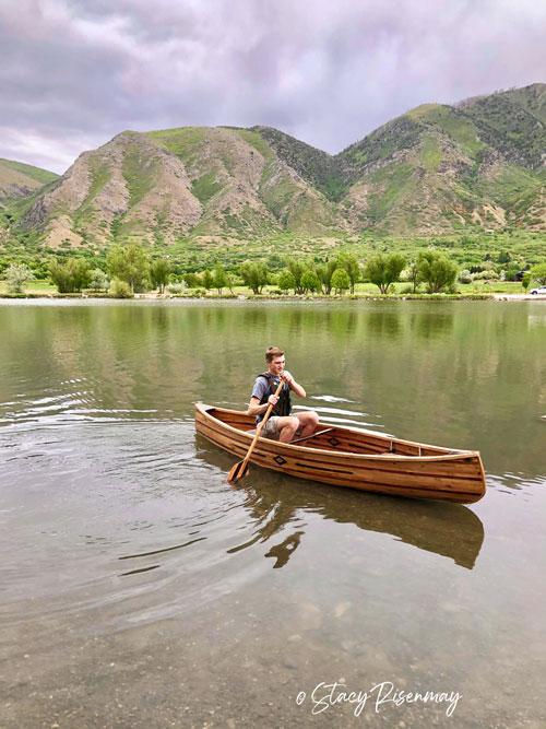 boy in wood canoe on a lake